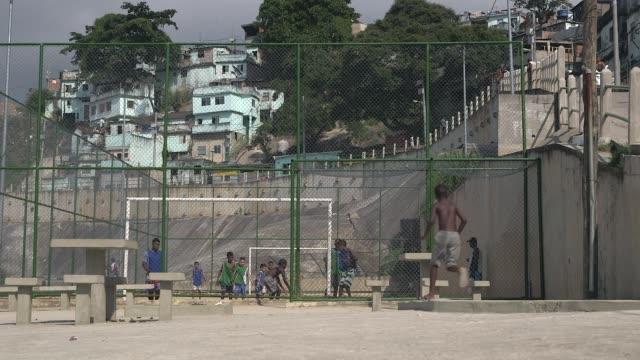 vídeos de stock, filmes e b-roll de long shot children of the morro da sao carlos favela play football under the supervision of their coach carlos in rio de janeiro brazil on june 6... - pipa brinquedo