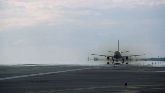vidéos et rushes de long shot commercial jet speeding down runway / medium shot pan taking off past cam - 1979