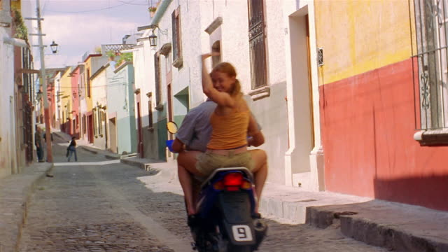 long shot couple on moped riding on cobblestone street past cam / woman turning to cam and waving - moped stock videos and b-roll footage