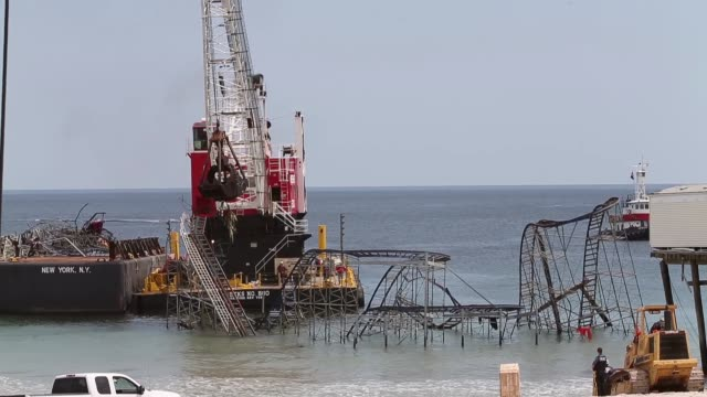 long shot crane dismantling the damaged roller coaster iconic jet star roller coaster damaged by hurricane sandy torn down on may 14 2013 in seaside... - dismantling stock videos and b-roll footage