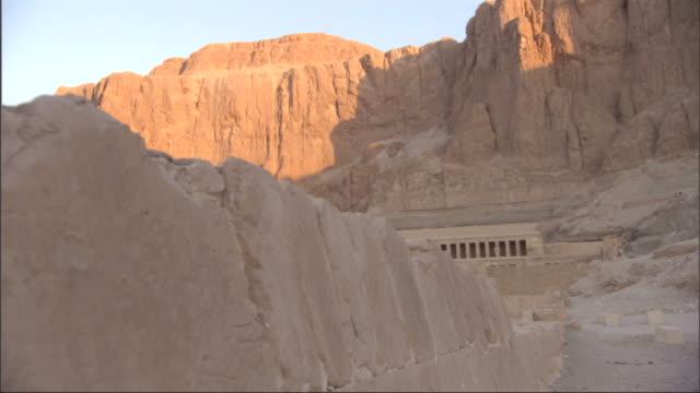 Long Shot, crane - Shadows cover a tomb beneath a mountain ridge