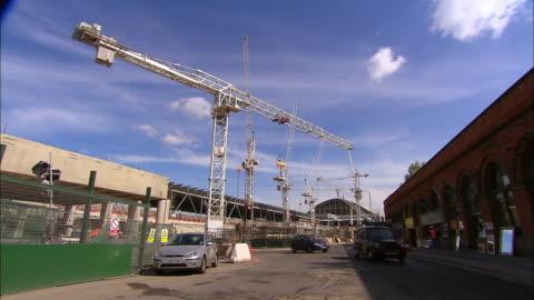 long shot cranes at construction site of eurostar terminal / traffic on street / london - eurotunnel folkestone stock-videos und b-roll-filmmaterial