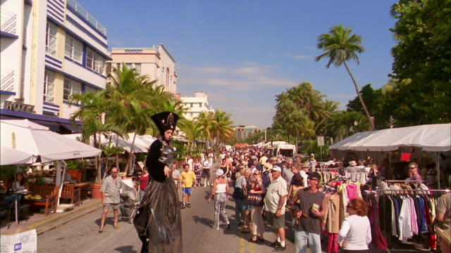 vídeos de stock, filmes e b-roll de long shot crowds at street fair / woman on stilts in costume walking toward cam and makes faces / miami beach - pintor artista