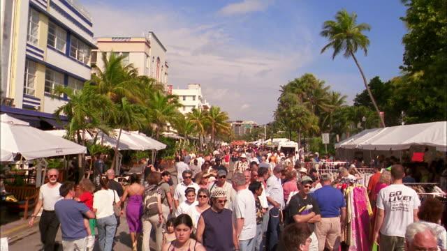 long shot crowds walking in street fair / miami beach, fl - オーシャンドライブ点の映像素材/bロール