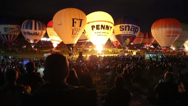 Long Shot Crowds watch as tethered balloons are illuminated by their burners during the night glow evening event at the Bristol International Balloon...