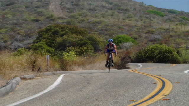 Long shot cyclist riding bike downhill on winding road