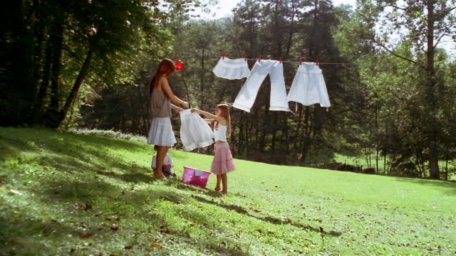 Long shot daughter helping mother hang laundry on clothesline / young boy sitting and watching