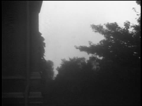 long shot destroyed german airplane falling over warsaw / trees in foreground / documentary - 1939 stock-videos und b-roll-filmmaterial