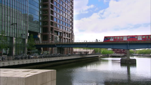 long shot docklands light railway (dlr) train crossing bridge over river thames at canary wharf / london - london docklands stock videos & royalty-free footage