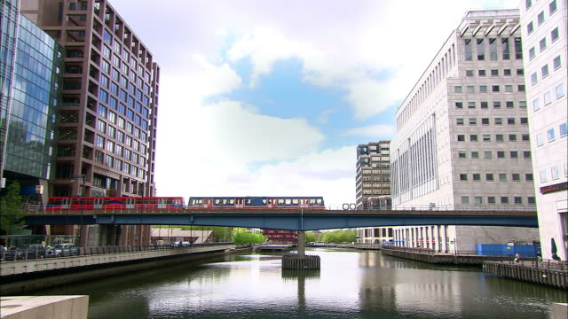 long shot docklands light railway (dlr) train crossing bridge over river thames at canary wharf / london - 2005 stock videos & royalty-free footage