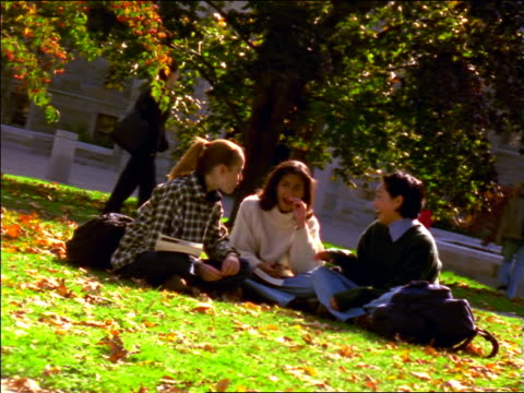 long shot dolly shot 3 female students (1 black, 1 asian) sitting on grass on college campus + talking / boston, ma - 女子大生点の映像素材/bロール