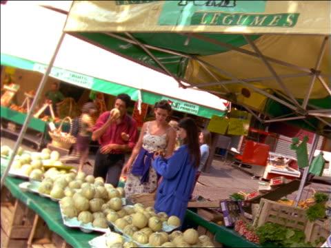 long shot dolly shot couple sampling melon from vendor in outdoor market / france - paar mittleren alters stock-videos und b-roll-filmmaterial