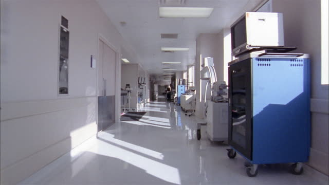 long shot dolly shot down hospital hallway past medical equipment - korridor stock-videos und b-roll-filmmaterial
