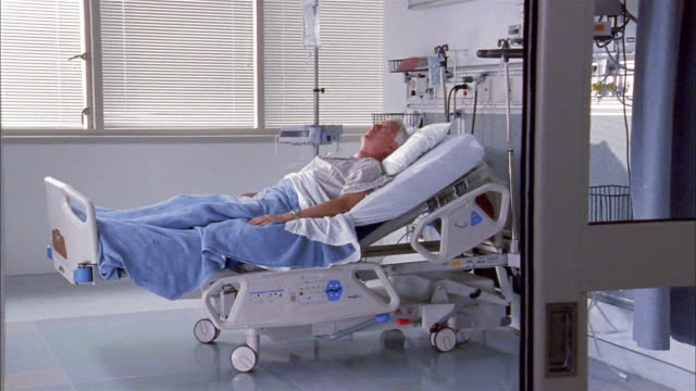 vídeos de stock e filmes b-roll de long shot dolly shot elderly man lying in hospital bed - one senior man only