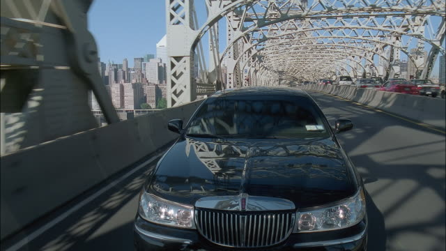 long shot dolly shot limousine driving on bridge away from city with manhattan skyline in background / new york city - dolly shot stock videos & royalty-free footage