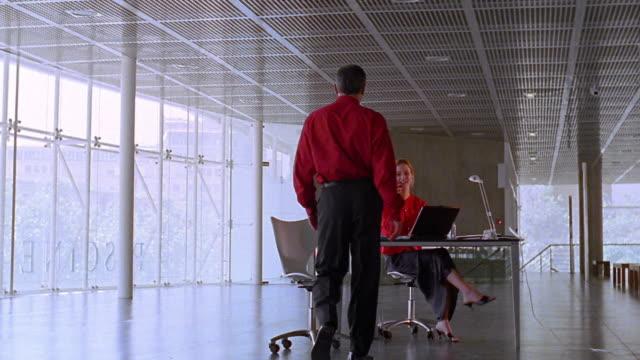 vídeos de stock e filmes b-roll de rear view long shot dolly shot man walking + greeting woman sitting at desk in open office - sentar se
