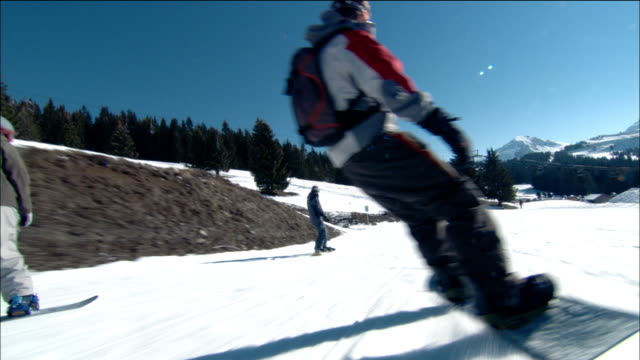 long shot dolly shot tracking shot man snowboarding downhill / crashing into another snowboarder and falling / morzine, france - snowboard stock-videos und b-roll-filmmaterial