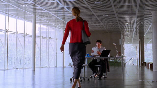 REAR VIEW long shot dolly shot woman walking into open office + greeting man sitting at desk in suit
