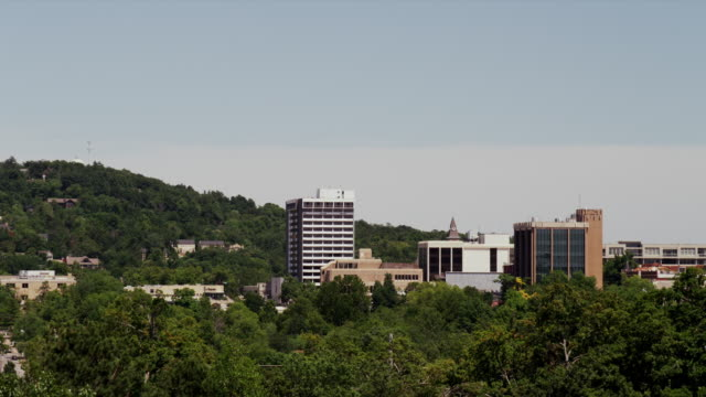 long shot, downtown buildings protrude from the trees forming the fayetteville ar skyline - arkansas stock videos & royalty-free footage