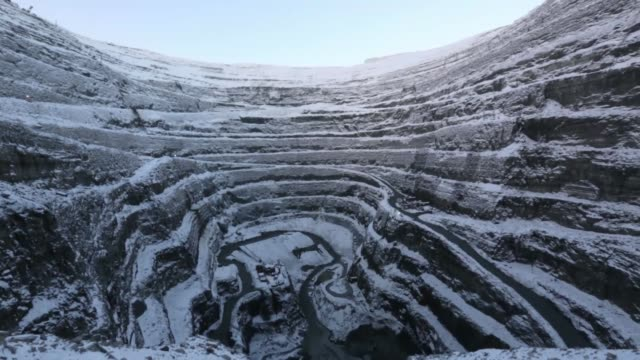 vidéos et rushes de long shot dump trucks carry diamond ore away from the base of the open pit at the udachny diamond mine operated by oao alrosa in udachny russia on... - diamant