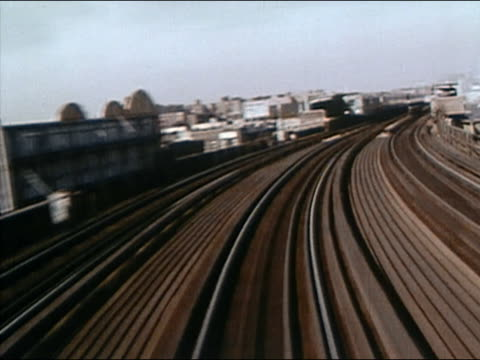 1968 long shot elevated train point of view speeding along / passing another train at station / skyline in background / audio - elevated train stock videos & royalty-free footage
