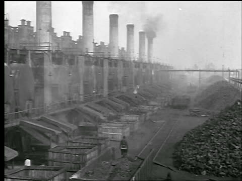 b/w 1929 long shot factory with smokestacks + piles of coal outside (tar factory?) / newsreel - 1929 stock videos & royalty-free footage