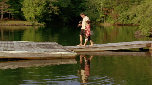 long shot father and son carrying fishing poles to end of dock / sitting down on edge with feet in water - clarkesville stock videos & royalty-free footage