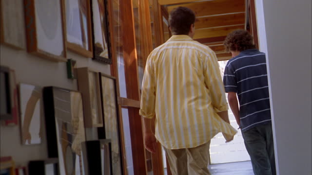 Long shot father and son walking down hall away from CAM + talking