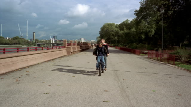 long shot father riding sons on bicycles along promenade / battersea park, london - battersea park stock videos & royalty-free footage