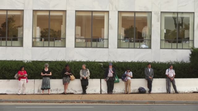 long shot federal workers wait outside the federal building along independence avenue during the first day of the federal government shutdown october... - federal building stock videos & royalty-free footage