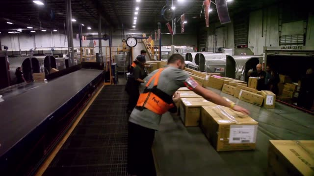 Long Shot FedEx employees sort through packages at a shipping center as they are heading out for delivery on Cyber Monday on December 2 2013 in Miami...