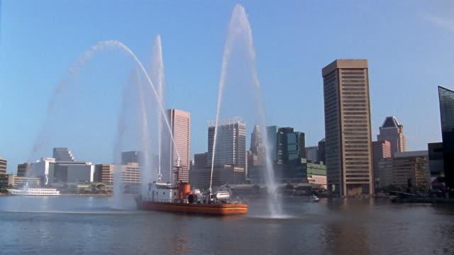 long shot fireboat spraying water in inner harbor / skyline in background / baltimore, maryland - hafen von baltimore stock-videos und b-roll-filmmaterial