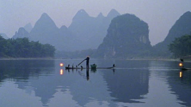 "long shot fisherman on ""sampan"" raft with cormorant fishing birds + lantern crossing li river / china - cormorant stock videos & royalty-free footage"