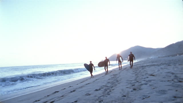 long shot four surfers carrying surfboards along beach towards cam with sunset in background - old diving suit stock videos and b-roll footage