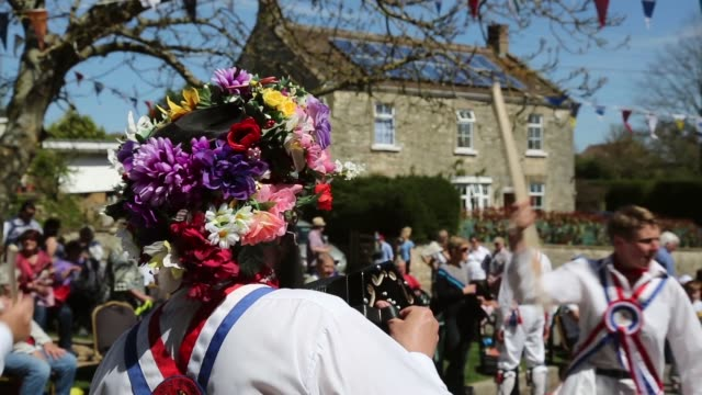vídeos de stock, filmes e b-roll de long shot from behind the musicians playing as morris men dance villagers celebrate traditional may bank holiday fayre on may 06 2013 in glastonbury... - 1 de maio