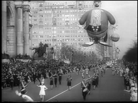B/W 1945 long shot giant balloons in air marching band at Macy's Thanksgiving Day parade / NYC / newsreel