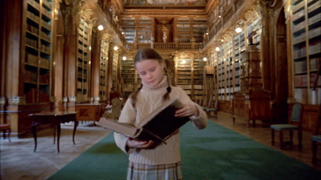 Long shot girl opening and reading book in Philosophical Hall library at Strahov Monastery / Prague
