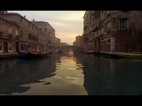 long shot gondola point of view travelling along canal and passing under footbridges at sunset / venice, italy - レターボックス点の映像素材/bロール