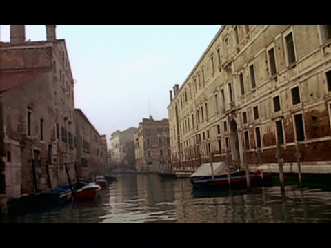 long shot gondola point of view travelling along canal past moored boats and buildings - レターボックス点の映像素材/bロール