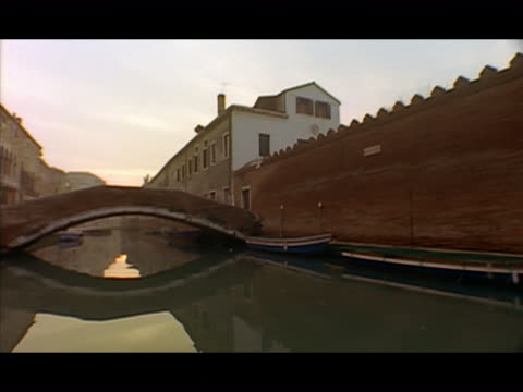 long shot gondola point of view turning onto canal and passing under footbridge at sunset / venice, italy - レターボックス点の映像素材/bロール
