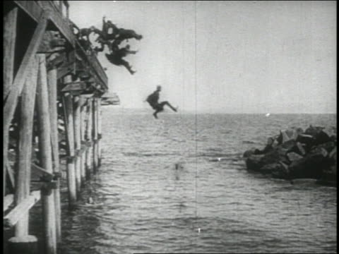 b/w 1914 long shot group of keystone kops jumping from pier into water . feature - 1914 stock videos & royalty-free footage