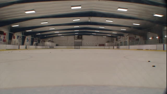 Long Shot hand-held - A hockey player skates toward the goal and shoots the puck. / North Carolina, USA