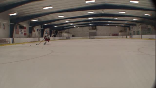 vídeos de stock e filmes b-roll de long shot hand-held - a hockey player skates toward the goal and shoots the puck, but misses. / north carolina, usa - pista de patinagem no gelo