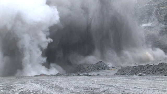long shot hand-held - explosives detonate in an open pit mine / gallivare, sweden - quarry stock videos and b-roll footage
