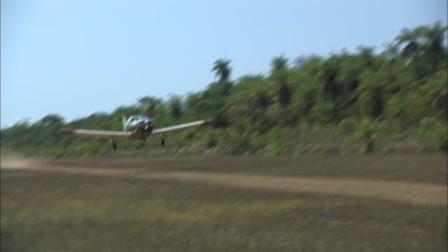 vídeos de stock, filmes e b-roll de long shot hand-held pan-right - a bush plane take off from a dirt runway in the amazon jungle. / brazil - pista de aterrizagem