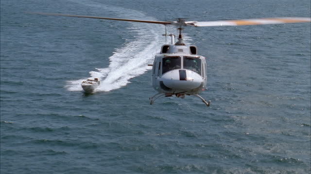 long shot helicopter flying over water towards camera followed by power boat - power boat stock videos & royalty-free footage