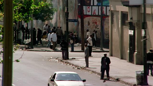Long shot homeless men loitering on street corner in Skid Row neighborhood of Los Angeles / California