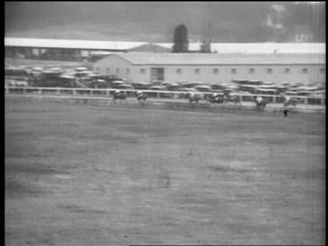b/w 1935 long shot pan horses racing around track - 1935 stock videos & royalty-free footage