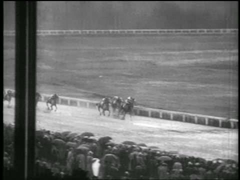 vidéos et rushes de b/w 1935 long shot pan jockeys on horses crossing finish line in race - 1935