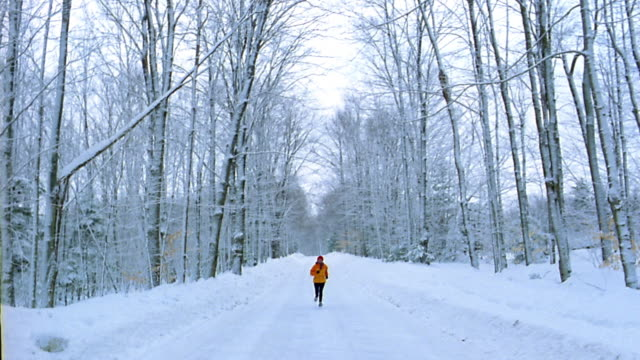 Long shot jogger running toward CAM on tree-lined snow-covered road / Vermont